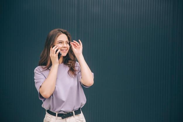 Fröhliche frau, die am telefon spricht und lächelt