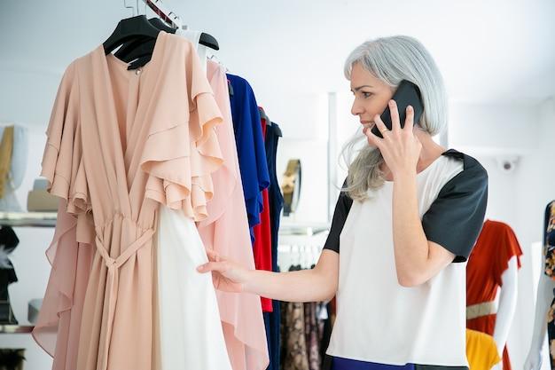 Fröhliche frau, die auf zelle spricht, während sie kleidung wählt und kleider auf gestell im modegeschäft durchsucht. mittlerer schuss. boutique-kunden- oder einzelhandelskonzept