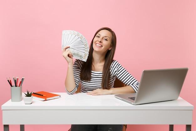 Fröhliche frau, die bündel viele dollar hält, bargeld, das an einem projekt im büro am weißen schreibtisch mit pc-laptop arbeitet?