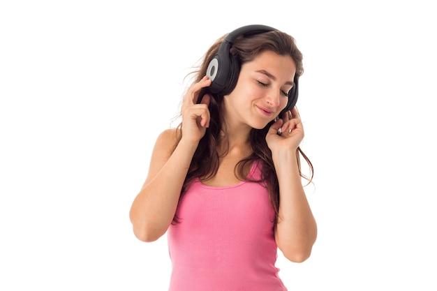 Fröhliche frau, die die musik mit kopfhörern lokalisiert auf weißer wand hört