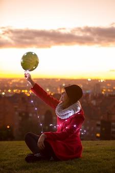 Fröhliche frau, die draußen auf dem boden sitzt und einen weihnachtsballon mit led-lichtern hält