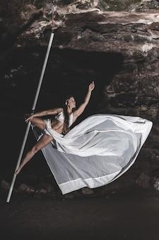 Fröhliche frau, die drinnen pole dance übt
