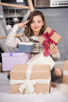Fröhliche frau, die ein weihnachtsgeschenk im wohnzimmer hält. h