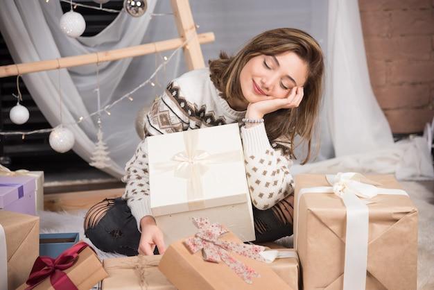 Fröhliche frau, die ein weihnachtsgeschenk im wohnzimmer hält.
