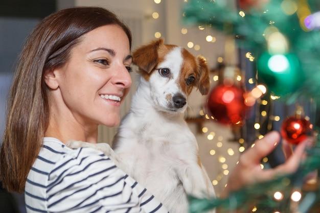 Fröhliche frau, die einen hund am heiligabend hält