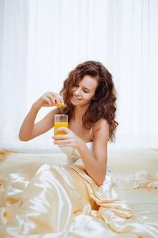 Fröhliche frau, die einen orangensaft trinkt, der auf ihrem bett zu hause sitzt