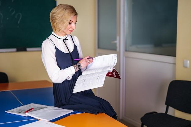 Fröhliche frau, die englisch im klassenzimmer in der nähe der tafel unterrichtet. englisch studieren. bildungskonzept.