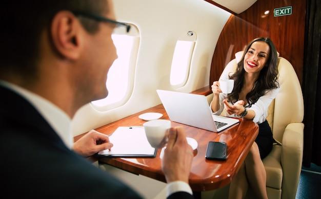 Fröhliche frau, die formelle kleidung und brille trägt, die etwas auf ihrem laptop tippt und telefoniert und mit ihrem kollegen in der business class fliegt.