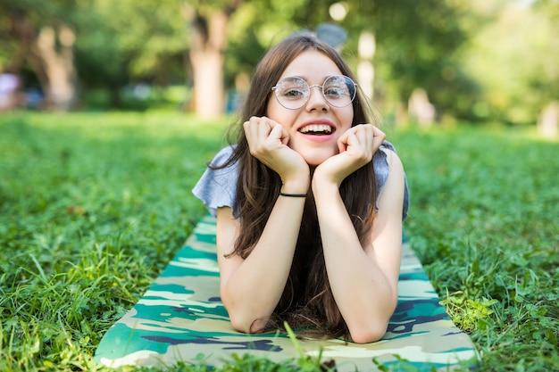 Fröhliche frau, die helles kleid trägt, das unten auf einem gras liegt