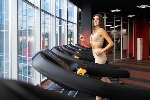 Fröhliche frau, die im fitnessstudio joggt