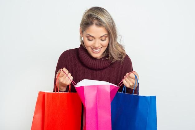 Fröhliche frau, die in einkaufstasche schaut