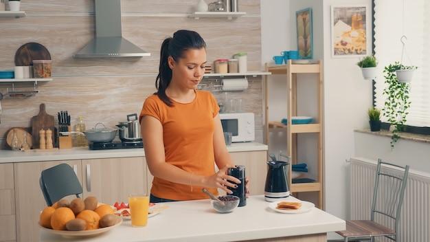 Fröhliche frau, die kaffeebohnen mahlt, um frischen kaffee zum frühstück zuzubereiten. hausfrau zu hause, die frisch gemahlenen kaffee in der küche zum frühstück zubereiten, trinken, kaffee-espresso mahlen, bevor sie zur arbeit geht