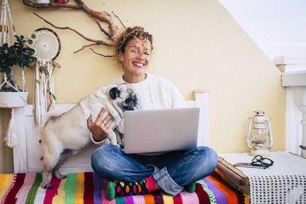 Fröhliche frau, die mit ihrem hund mops spielt, während sie von der hausterrasse aus am laptop arbeitet. frau, die spaß beim spielen mit süßem mops hat, während sie von zu hause aus am laptop arbeitet