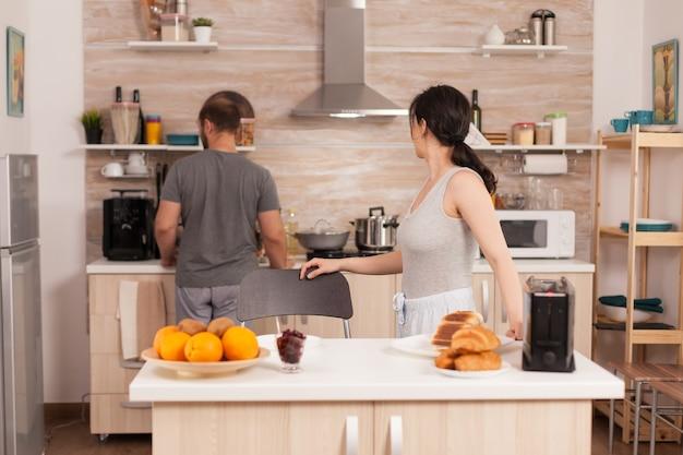 Fröhliche frau, die mit ihrem mann in der küche spricht, während sie das brot zum frühstück toastet. junges paar am morgen, das essen zusammen mit zuneigung und liebe zubereitet