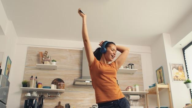 Fröhliche frau, die morgens in der küche singt. energiegeladene, positive, fröhliche, lustige und süße hausfrau, die alleine im haus tanzt. unterhaltung und freizeit allein zu hause