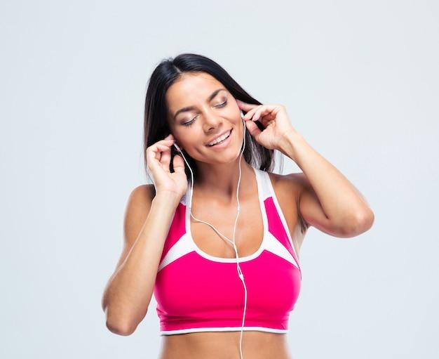Fröhliche frau, die musik in kopfhörern hört