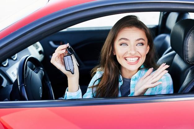 Fröhliche frau, die rotes auto fährt und auto kauft. glücklicher besitzer des neuen autos, beiseite schauend, schlüssel vom auto haltend und lächelnd. kopf und schultern, glücklicher fahrer