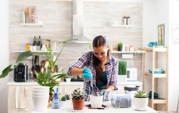 Fröhliche frau, die sich um hausblumen kümmert, sitzt in der küche auf dem tisch