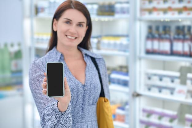 Fröhliche frau, die smartphone-bildschirm in der apotheke zeigt
