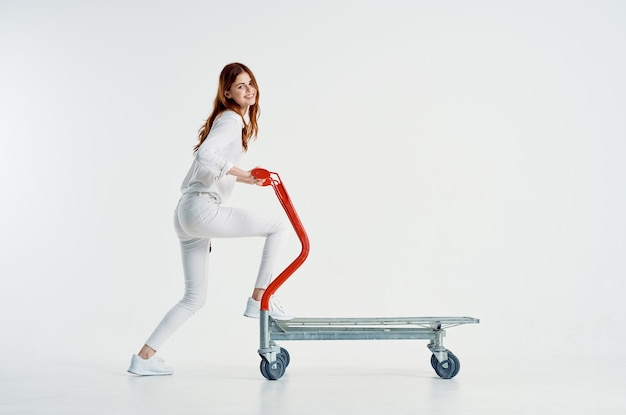 Fröhliche frau, die supermarkt-trolley-wagen fährt