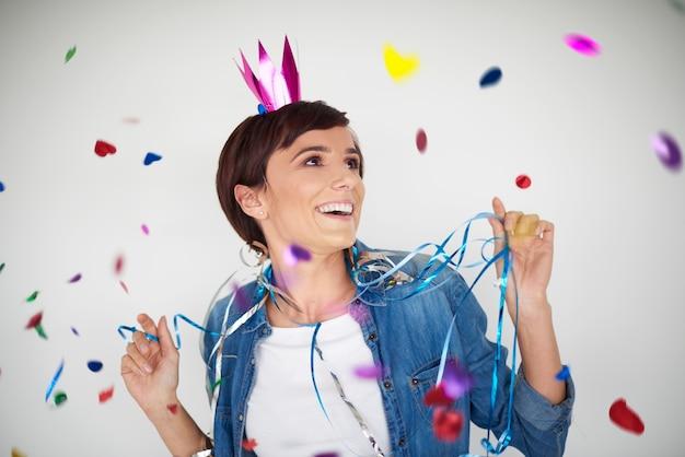 Fröhliche frau, die unter bunten konfettistücken tanzt