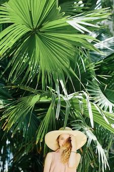 Fröhliche frau, die unter palme steht