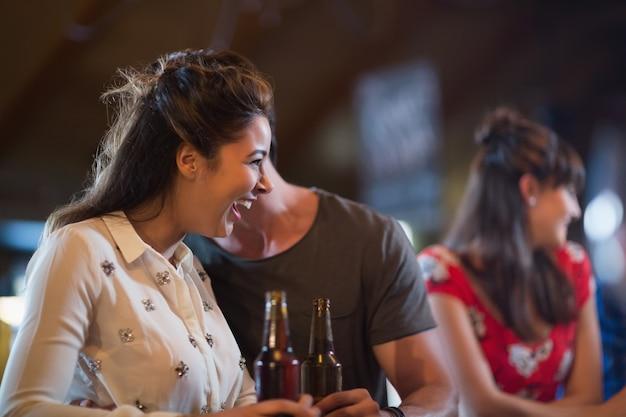 Fröhliche frau, die weg schaut, während bierflasche hält