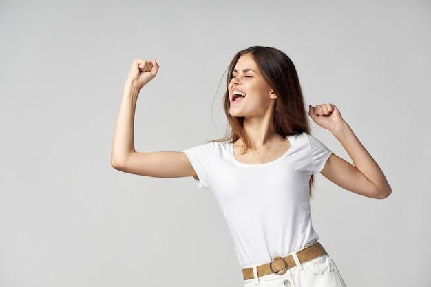 Fröhliche frau emotionen gestikulieren hände studio weißes t-shirt