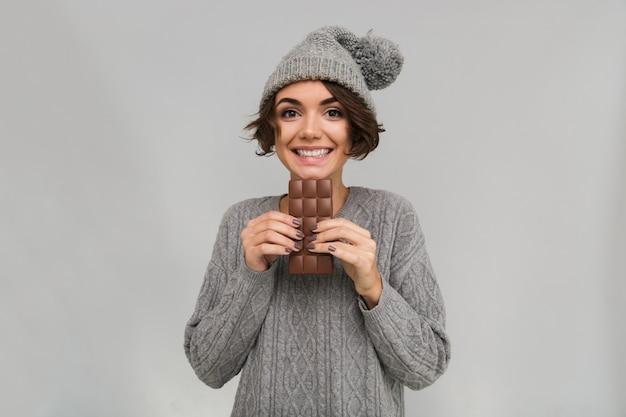 Fröhliche frau gekleidet in pullover und warmem hut, der schokolade hält.