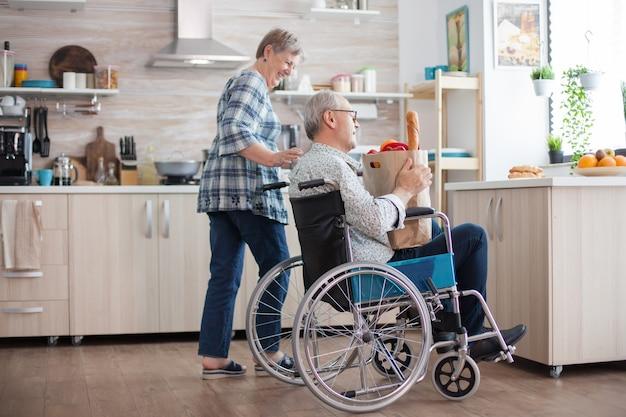 Fröhliche frau hilft behinderten ehemann in der küche. ältere frau, die lebensmittelpapiertüte vom behinderten ehemann im rollstuhl nimmt. reife leute mit frischem gemüse vom markt. leben mit behinderung