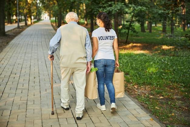 Fröhliche frau hilft beim einkaufen für den alten mann