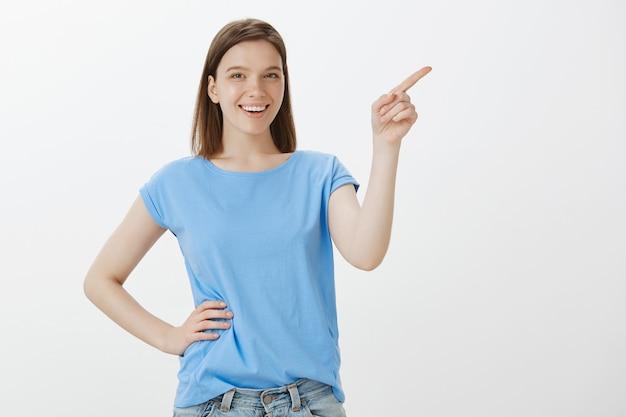 Fröhliche frau im blauen t-shirt, das obere rechte ecke zeigt und ihr logo zeigt