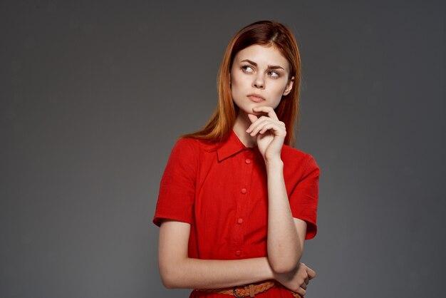 Fröhliche frau im eleganten stil des roten kleiderstudios