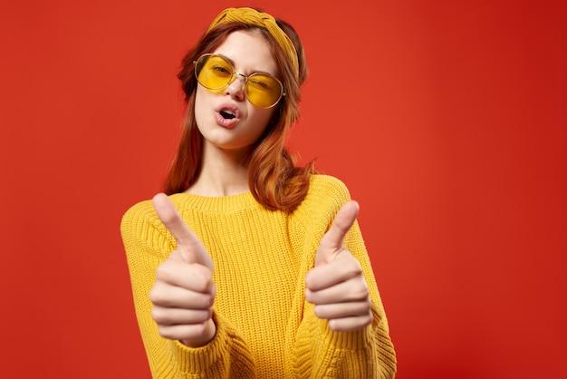 Fröhliche frau im gelben brillenpullover hipster mode retro-stil. foto in hoher qualität