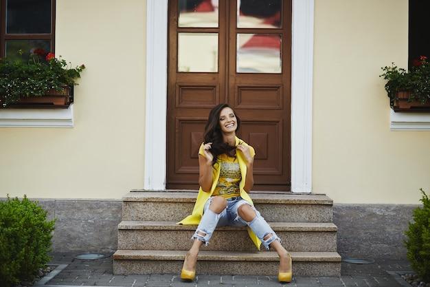 Fröhliche frau im gelben lässigen outfit, das auf der treppe sitzt