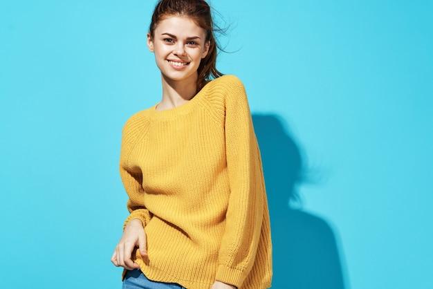 Fröhliche frau im gelben pullover freizeitkleidung spaß beschnittene ansicht blauen hintergrund.