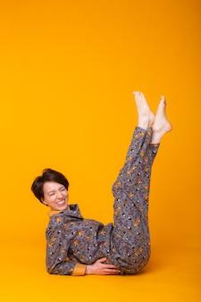 Fröhliche frau im haus tragen pyjama in der gelben wand