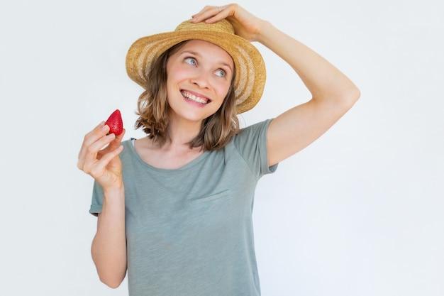 Fröhliche frau im hut, die reife erdbeere hält und lächelt