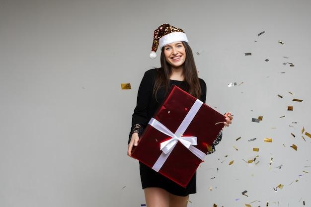 Fröhliche frau im schwarzen kleid und im weihnachtshut freut sich der schachtel mit ihrem weihnachtsgeschenk mit viel konfetti um sie herum