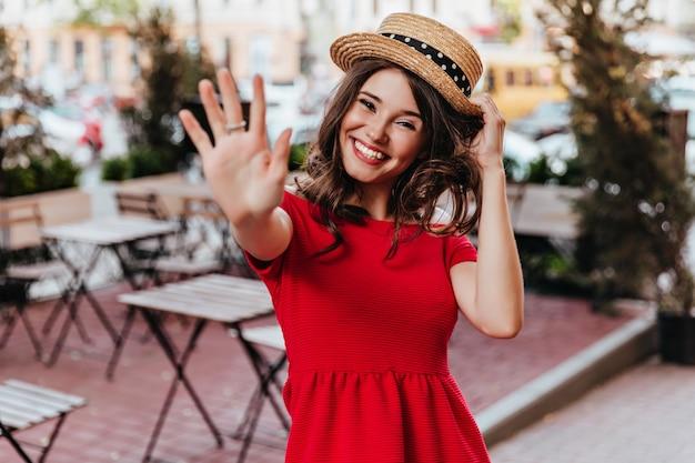 Fröhliche frau im strohhut und im roten kleid, die hand zur kamera winken. blithesome süßes mädchen, das gute gefühle ausdrückt.