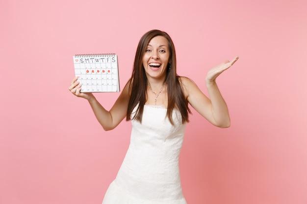 Fröhliche frau im weißen kleid, die hände ausbreitet und den kalender der weiblichen perioden hält, um die menstruationstage zu überprüfen