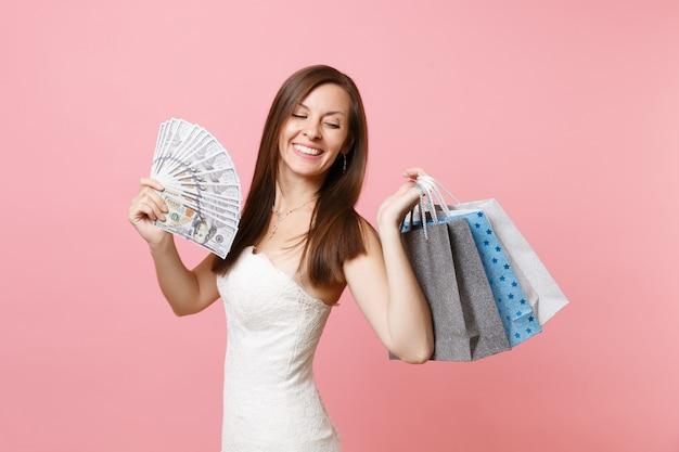 Fröhliche frau im weißen kleid hält bündel viele dollar, bargeld, mehrfarbige pakettaschen mit einkäufen nach dem einkaufen?
