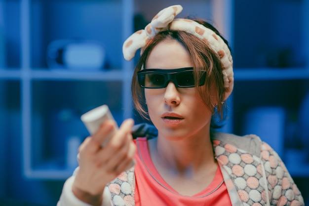 Fröhliche frau in 3d-gläsern, die popcorn essen. lustige junge frau in den 3d-gläsern, die filmfilm ansehen, popcorn essen.