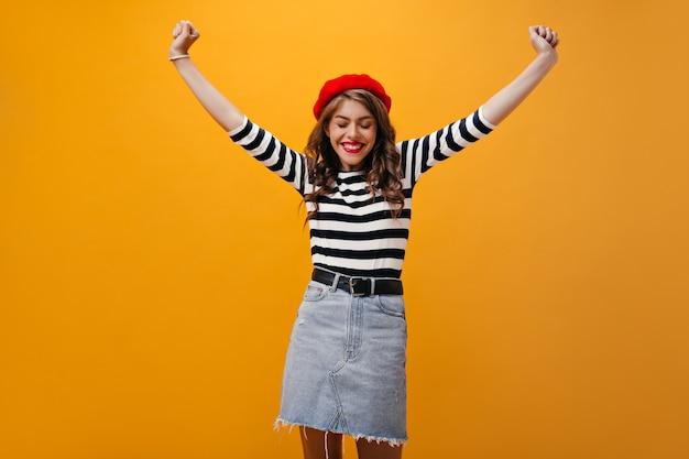 Fröhliche frau in baskenmütze und hemd, die glücklich auf orange hintergrund aufwirft. positives süßes mädchen mit dem lockigen haar und den roten lippen, die aufwerfen.