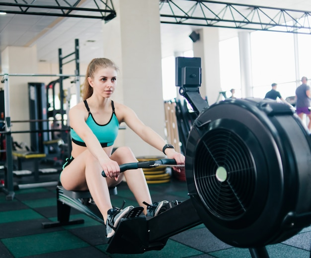 Fröhliche frau in der sportbekleidung, die übung im rudersimulationsgerät in einem fitnessstudio tut.