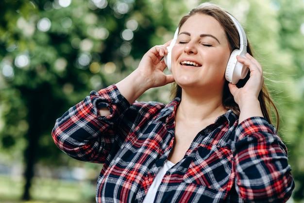 Fröhliche frau in drahtlosen kopfhörern singt ihr lieblingslied