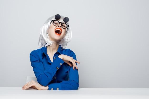 Fröhliche frau in einer weißen perücke rote lippen dunkle brille sitzt an einem tisch in einem blauen hemd