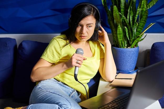 Fröhliche frau in freizeitkleidung aufnahme eines podcasts, der in ein mikrofon mit kopfhörern und laptop, notizbuch spricht