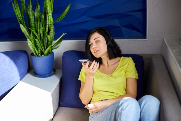 Fröhliche frau in freizeitkleidung mit kopfhörern und smartphone, aufnahme zum podcast auf dem sofa zu hause. weiblicher podcaster live-streaming, frau spricht im clubhaus.