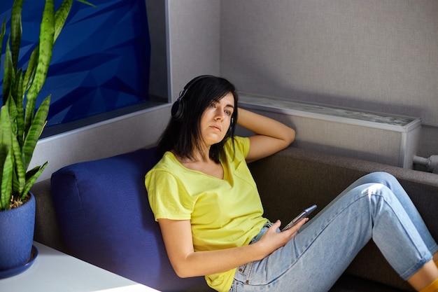 Fröhliche frau in freizeitkleidung mit kopfhörern und smartphone, podcast auf sofa zu hause hörend.